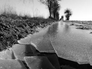 Gebrochenes Eis am Feldweg